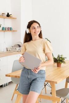 Mulher sorridente a ouvir música em casa