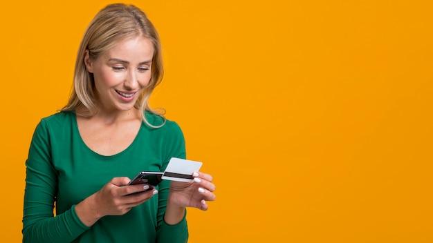Mulher sorridente a preencher as informações do cartão de crédito no smartphone