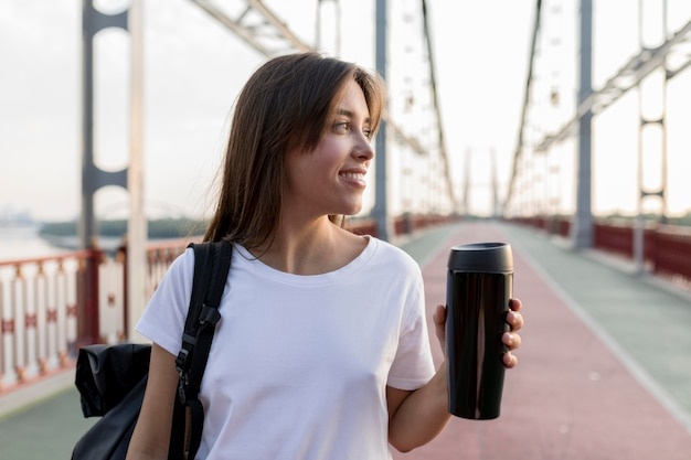 Mulher sorridente a viajar segurando uma garrafa térmica na ponte