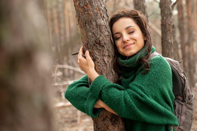 Mulher sorridente, abraçando, árvore