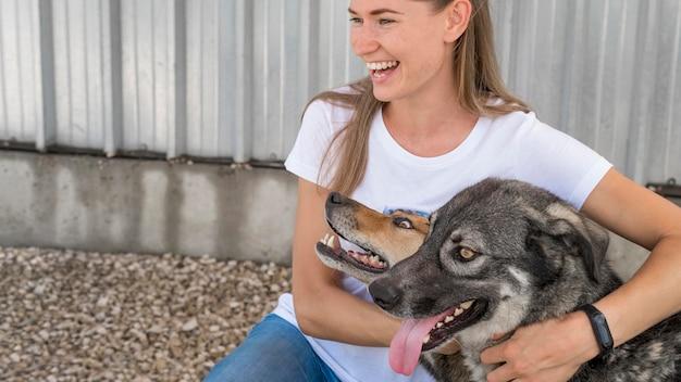 Mulher sorridente abraçando cachorros de resgate fofos