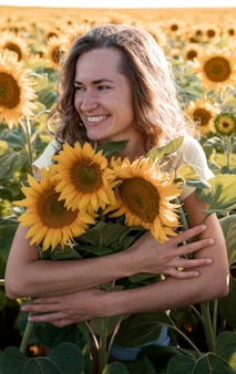 Mulher sorridente abraçando girassóis