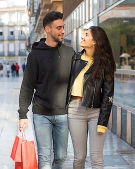 Mulher sorridente, abraçando, jovem, positivo, homem, com, shopping, pacotes