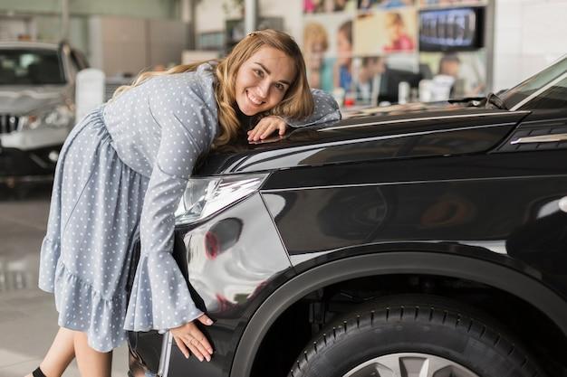 Mulher sorridente, abraçando o carro moderno
