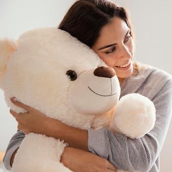 Mulher sorridente abraçando o grande ursinho de pelúcia em casa