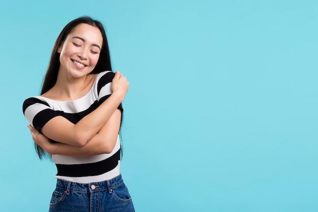 Mulher sorridente, abraçando-se