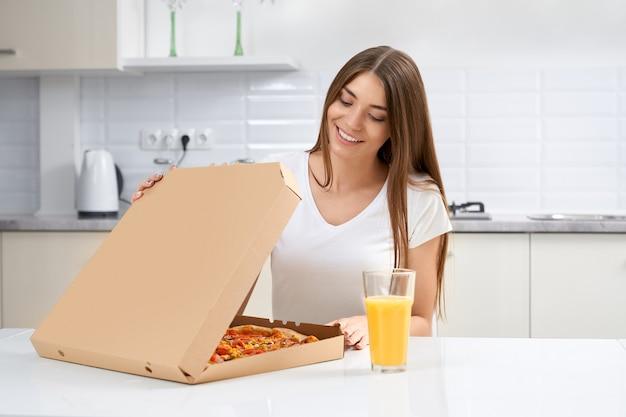 Mulher sorridente abrindo caixa com pizza na cozinha