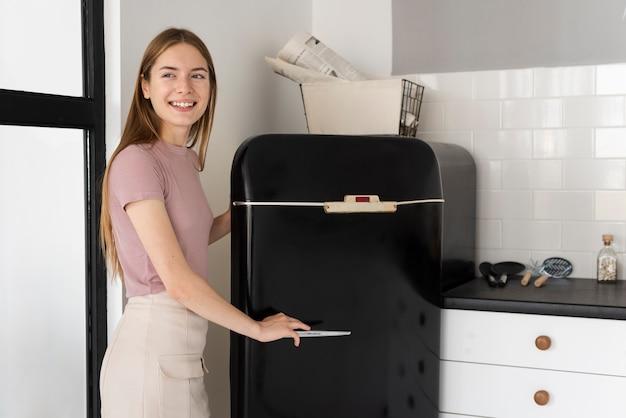 Mulher sorridente, abrindo sua geladeira