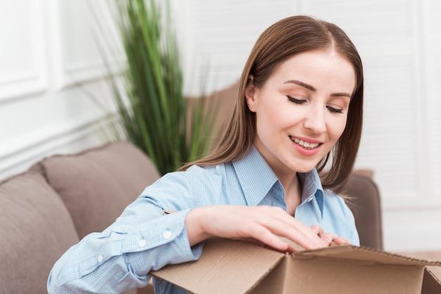 Mulher sorridente, abrindo um pacote dentro de casa