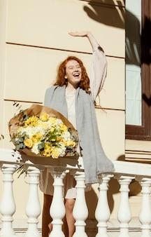 Mulher sorridente acenando ao ar livre com um buquê de flores da primavera
