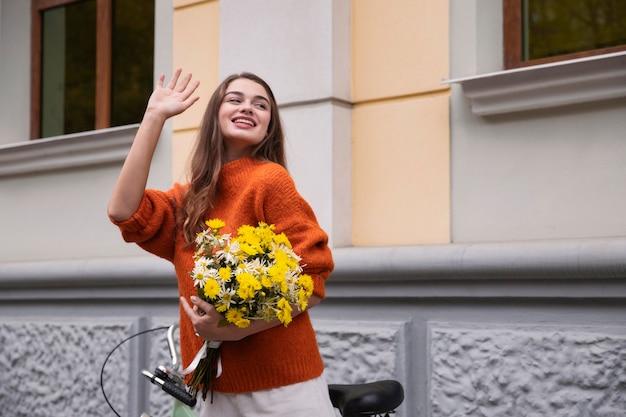 Mulher sorridente acenando enquanto segura um buquê de flores ao lado da bicicleta