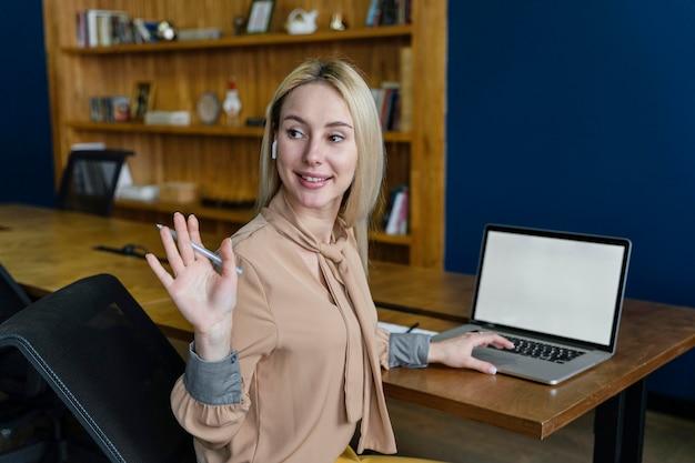 Mulher sorridente acenando no escritório enquanto trabalha no laptop