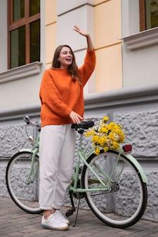 Mulher sorridente acenando sentado ao lado de uma bicicleta ao ar livre
