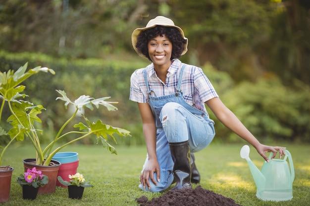 Mulher sorridente, agachando-se no jardim, olhando para a câmera