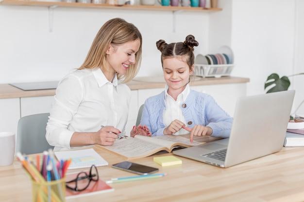 Mulher sorridente, ajudando a filha a estudar em casa