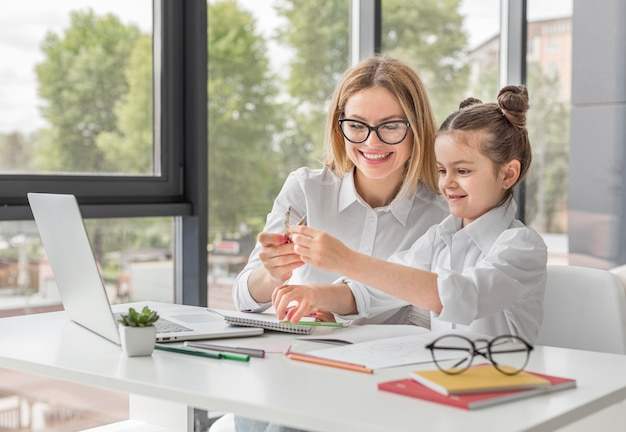 Mulher sorridente, ajudando a filha com a lição de casa