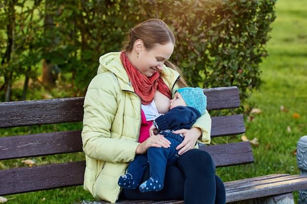 Mulher sorridente amamentando bebê no parque