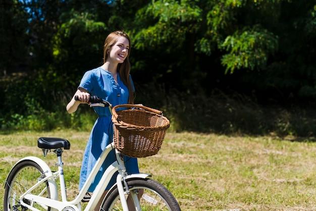 Mulher sorridente andando ao lado de sua bicicleta