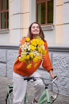Mulher sorridente andando de bicicleta ao ar livre com um buquê de flores