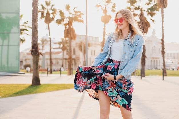 Mulher sorridente andando na rua da cidade com saia estampada elegante e jaqueta jeans grande e óculos de sol rosa
