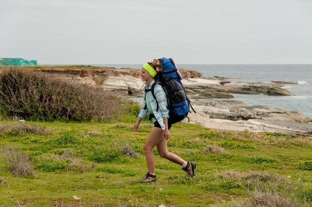 Mulher sorridente andando nas pedras com mochila para caminhadas