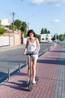 Mulher sorridente, andar de scooter