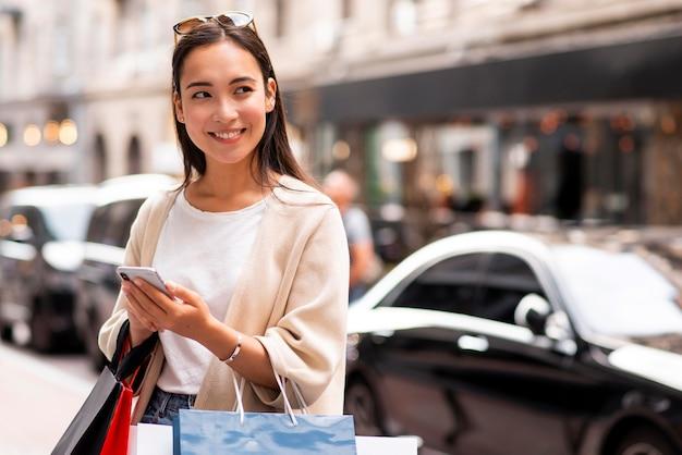 Mulher sorridente ao ar livre com smartphone e carregando sacolas de compras