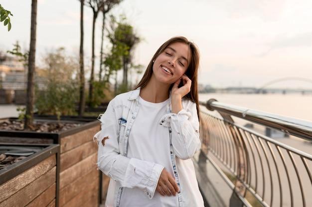 Mulher sorridente ao ar livre ouvindo música nos fones de ouvido
