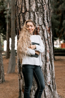 Mulher sorridente ao lado de uma árvore, segurando um livro
