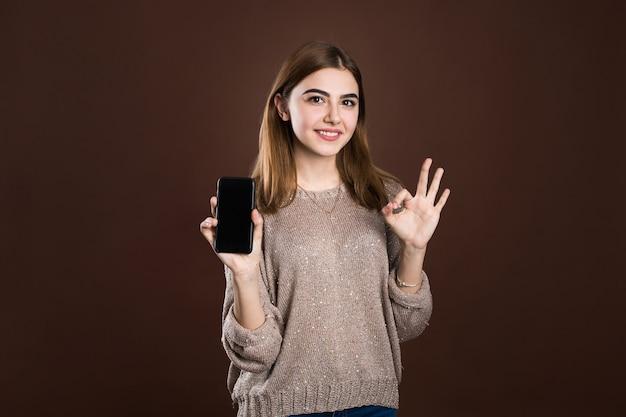 Mulher sorridente apontando em um smartphone em um fundo marrom