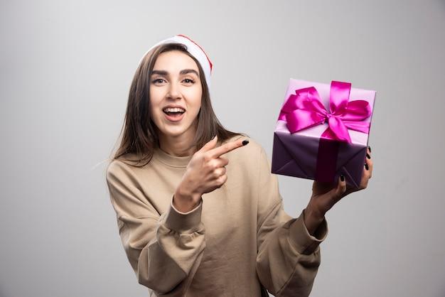 Mulher sorridente, apontando para uma caixa de presente de natal.