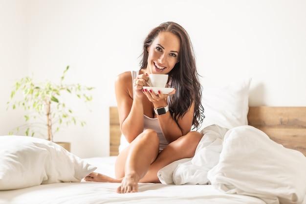 Mulher sorridente aprecia seu café da manhã depois de acordar ainda sentada em uma cama.