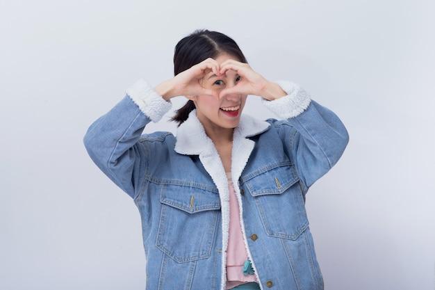 Mulher sorridente asiática, mostrando a mão com sinal de coração, garota caucasiana positiva, vestindo roupas casuais azuis