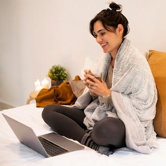 Mulher sorridente assistindo a um programa de tv no laptop