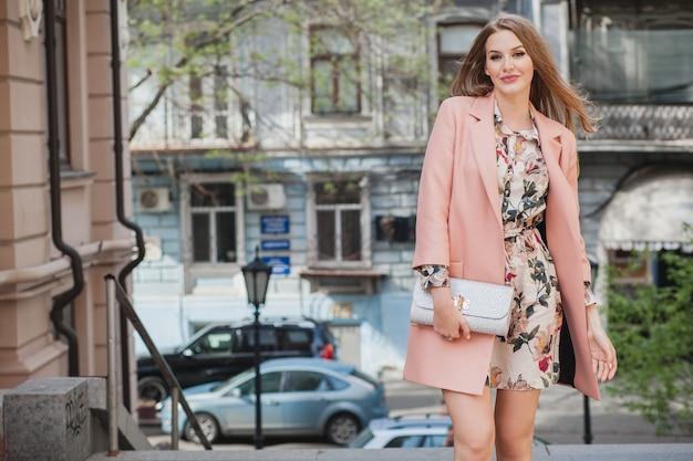 Mulher sorridente atraente andando pelas ruas da cidade com casaco rosa tendência da moda de primavera segurando a bolsa