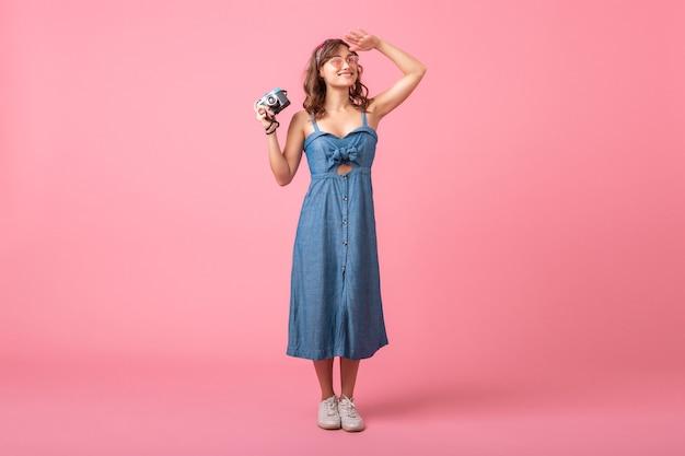 Mulher sorridente atraente ansiosa tirando foto na câmera vintage com vestido jeans isolado no fundo rosa