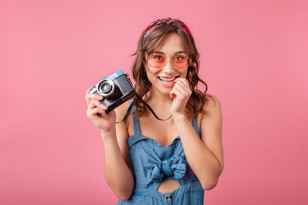 Mulher sorridente atraente com expressão emocional engraçada no rosto com câmera vintage em vestido jeans e óculos escuros isolados no fundo rosa