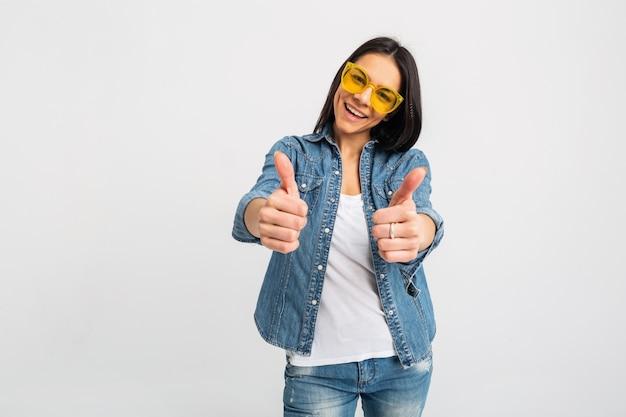 Mulher sorridente atraente com os polegares para cima isolados no branco