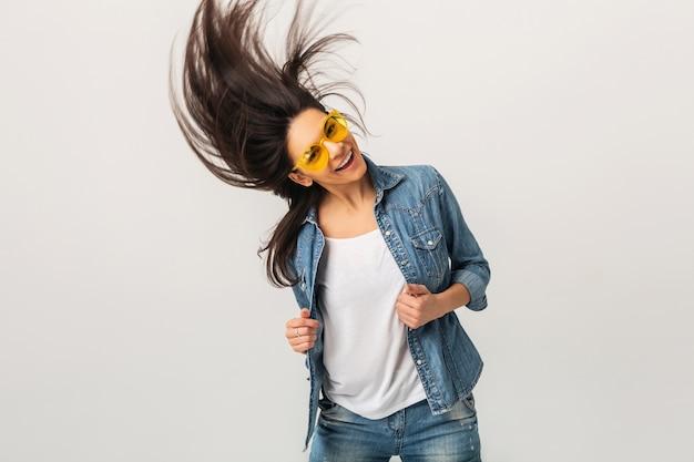 Mulher sorridente atraente dançando acenando cabelo comprido isolado no estúdio branco