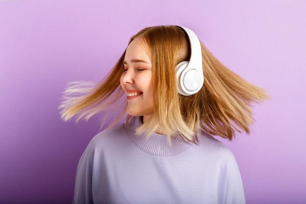 Mulher sorridente atraente dançando em fones de ouvido com penteado de cabelo loiro a voar. menina adolescente gosta de ouvir música em movimento em fones de ouvido sem fio isolados sobre o fundo de cor roxa.