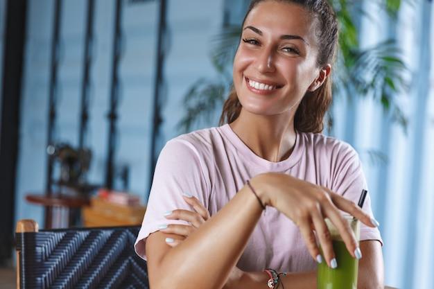 Mulher sorridente atraente de férias, aproveitando o resort paradisíaco, senta-se em um café usando telefone celular e bebendo um smoothie saudável.