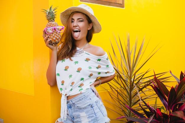 Mulher sorridente atraente de férias em t-shirt estampada com chapéu de palha na moda do verão, mãos segurando abacaxi