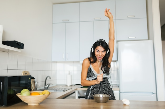 Mulher sorridente atraente de pijama cozinhando café da manhã na cozinha, estilo de vida saudável, ouvindo música em fones de ouvido, cantando, dançando, se divertindo