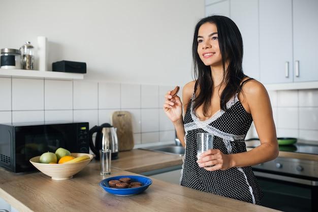 Mulher sorridente atraente de pijama tomando café da manhã na cozinha, comendo biscoitos e bebendo leite, estilo de vida saudável