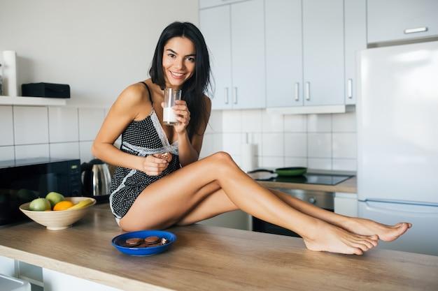 Mulher sorridente atraente de pijama tomando café da manhã na cozinha pela manhã, comendo biscoitos e bebendo leite, estilo de vida saudável, pernas longas e magras