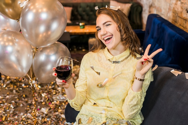 Mulher sorridente atraente desfrutando de festa segurando o copo de vinho