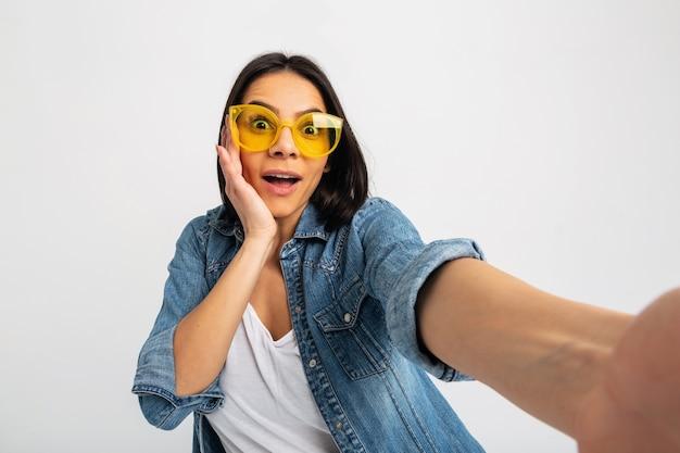 Mulher sorridente atraente e animada fazendo selfie com rosto chocado isolado no branco