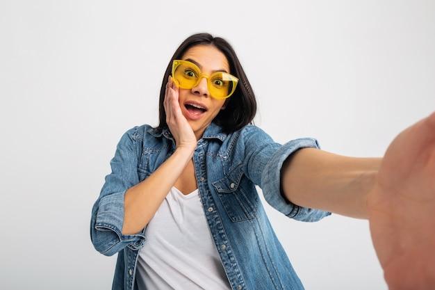 Mulher sorridente atraente e animada fazendo selfie com rosto surpreso isolado no branco