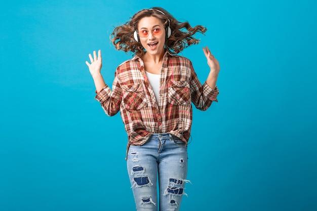 Mulher sorridente atraente e emocional pulando com uma expressão engraçada de cara maluca. camisa quadriculada e jeans isolado no fundo azul do estúdio, usando óculos de sol rosa