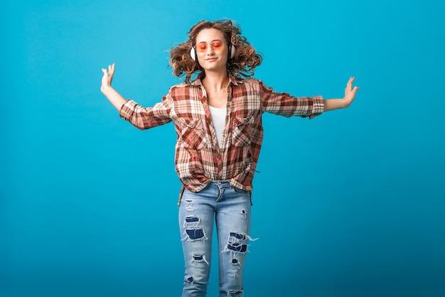 Mulher sorridente atraente e emocional pulando com uma expressão engraçada de cara maluca em uma camisa quadriculada e calça jeans isolada no fundo azul do estúdio, usando óculos de sol rosa, saiu olhando para cima